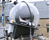 Weather-proof enclosure domes for intelligent lighting units for temporary roof top installation